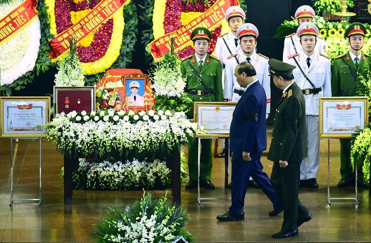 Thủ tướng Nguyễn Xuân Phúc và Bộ trưởng Tô Lâm đi tới linh cữu của thượng úy Dương Đức Hoàng Quân, sinh năm 1992. Ảnh: Giang Huy