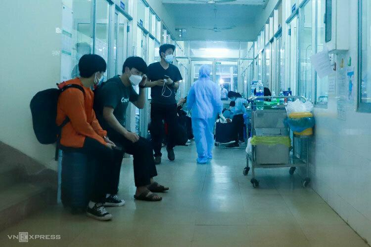 Nhóm khách Daegu để valy và đứng ở lối đi trong khu cách ly để phản ứng, chiều 24/2. Ảnh: Nguyễn Đông.