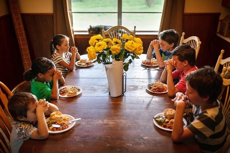Các con của Mossbarger cầu nguyện trước khi ăn. Ảnh: NYTimes.
