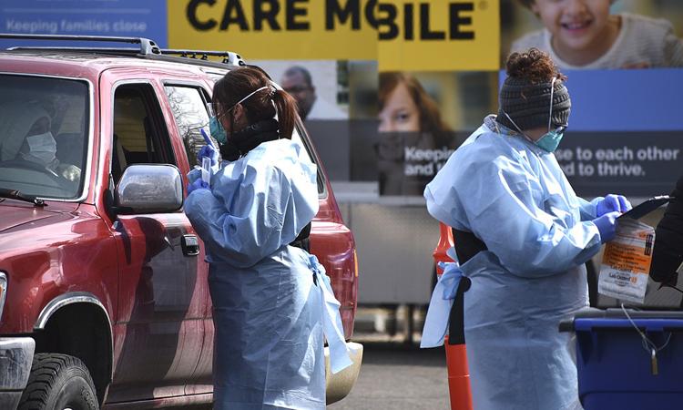 Hai nhân viên y tế chuẩn bị lấy mẫu xét nghiệm cho tài xế ở Billings, bang Montana hôm 20/3. Ảnh: AP.