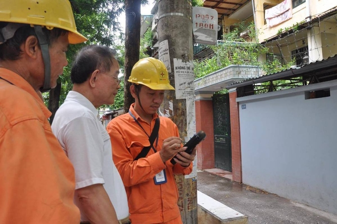 Công nhân Tổng công ty Điện lực Hà Nội ghi chỉ số công tơ từ thiết bị đo xa HHU dưới sự giám sát của người dân. Ảnh: Minh Hà