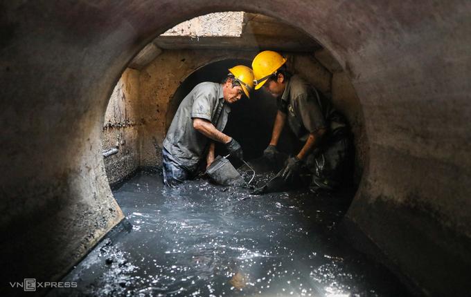 Cha con ông Nguyễn Phú Hộ (53 tuổi) móc bùn thải tại một cống thoát nước trên đường Nguyễn Ảnh Thủ, quận 12, TP HCM, ngày 14/8. Ảnh: Quỳnh Trần