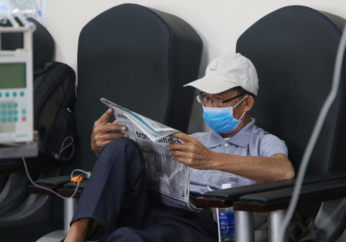 Ông Chung Văn Vui đọc báo khi đang truyền hóa chất điều trị ung thư dạ dày. Ảnh Thư Anh