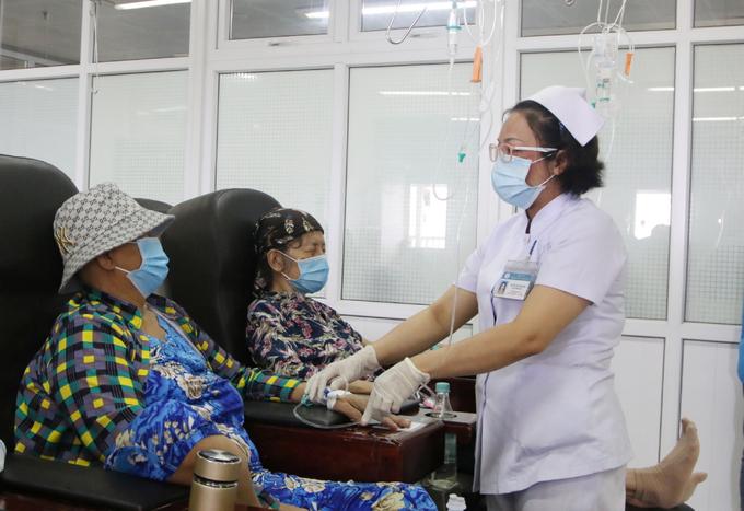 Nhân viên y tế đi lại như con thoi giữa các hàng ghế, hỏi thăm tình hình bệnh nhân, kiểm tra và điều chỉnh lượng thuốc. Ảnh Thư Anh