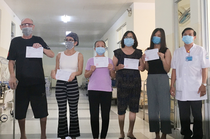 Các bệnh nhân Covid-19 cuối cùng điều trị tại Bệnh viện Bệnh Nhiệt đới TP HCM nhận giấy ra viện ngày 31/8. Ảnh: Thư Anh.