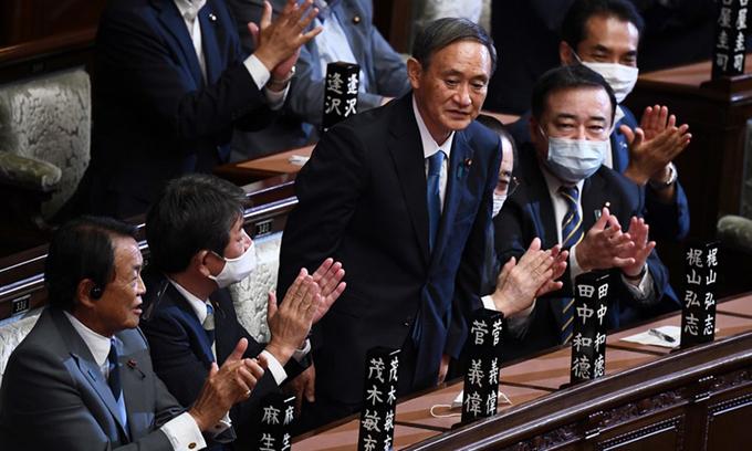 Ông Yoshihide Suga (giữa) được vỗ tay hoan nghênh sau khi kết quả kiểm phiếu tại quốc hội hôm nay cho thấy ông trở thành thủ tướng Nhật. Ảnh: AFP.