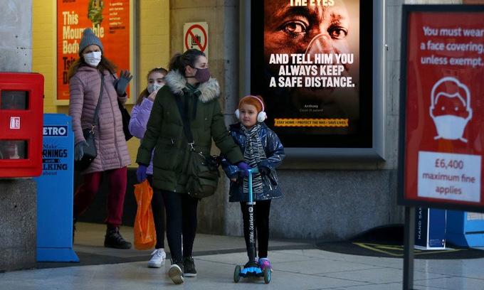 Người dân Anh đi giữa các biển hiệu kêu gọi phòng chống Covid-19 ở London hôm 25/1. Ảnh: AFP.