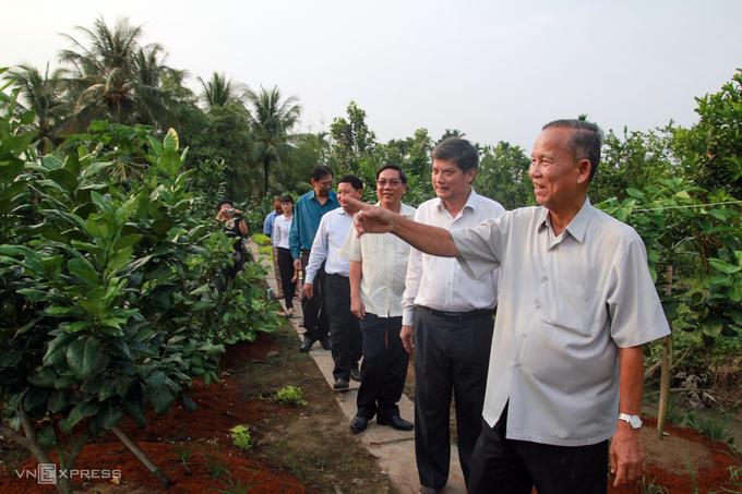 Nguyên Phó thủ tướng Trương Vĩnh Trọng dẫn đoàn khách đến từ TP HCM thăm khu vườn cây ăn trái tại nhà ở Bến Tre, năm 2018. Ảnh: Hữu Khoa
