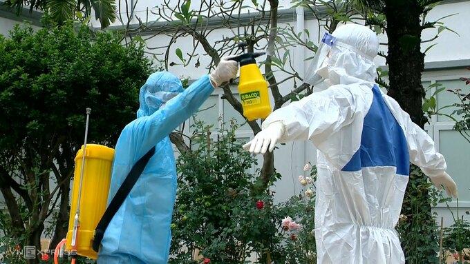 Nhân viên y tế phun khử khuẩn trước khi tiến hành lấy mẫu xét nghiệm. Ảnh: Thế Quỳnh