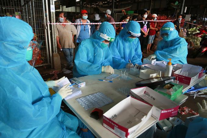 Nhân viên y tế đang lấy mẫu xét nghiệm ở chợ đầu mối Bình Điền, quận 8, ngày 5/7. Ảnh: Quỳnh Trần.