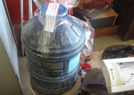 Bình chứa hóa chất màu xanh phát hiện tại nhà bà Hiên.