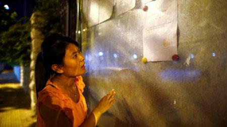 Một phụ nữ đọc bảng thông báo về phiên tòa xét xử ôg Bạc trên bảng tin của tòa án.